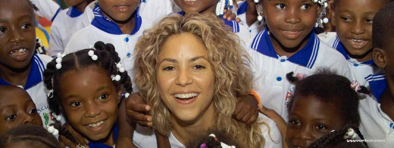 Shakira pop star being embraced by children smiling